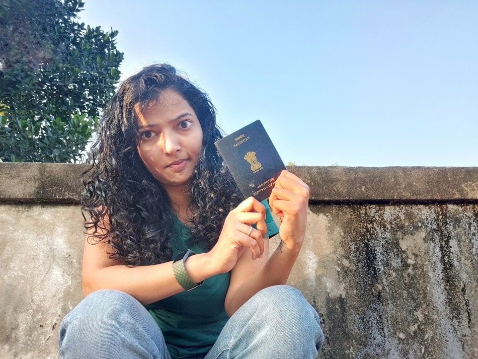 A woman sitting down holding Indian passport