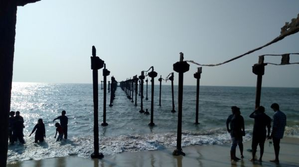 An old pier on Alleppey beach while people hang around