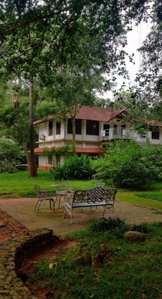 Cast iron chairs in front of a white building with red tiled roof surrounded by trees is Center guest house in Auroville