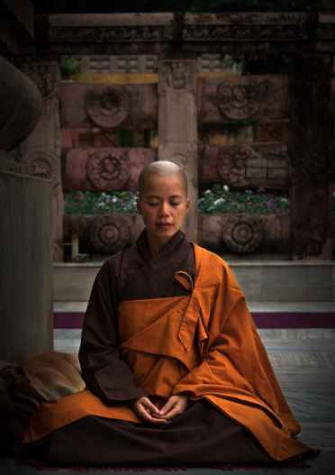 selective focus photography of monk during meditation