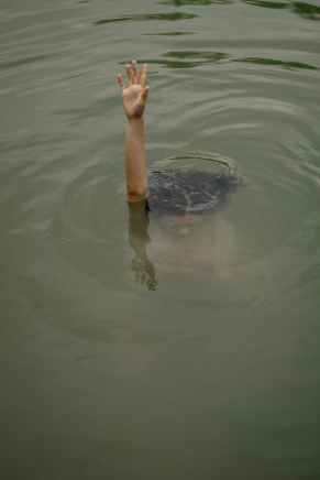 person in black shorts floating on water