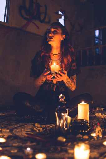 spooky witch among candles during ritual