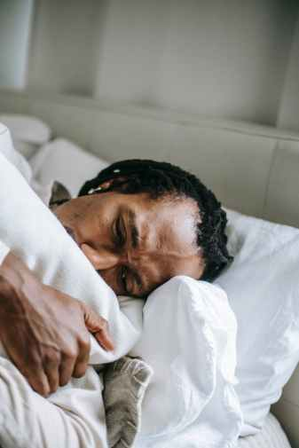 uncertain stressed black man hugging pillow on bed