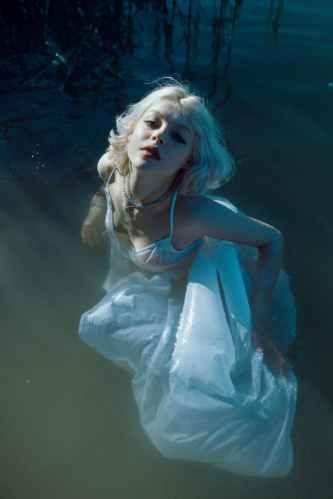 serene young woman in maxi dress swimming in lake