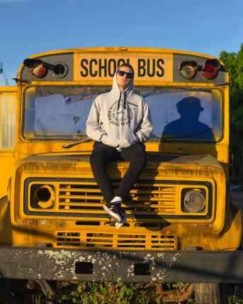 man sitting on a hood of a school bus