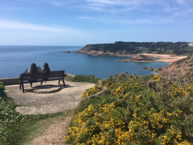 two women sat on a bench in Jersey overlooking the sea on a beautiful summer's day