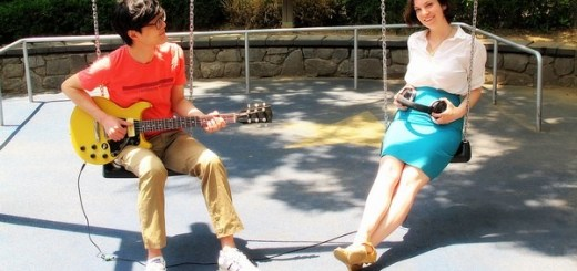 Rocking Out with New Member Baby Announcement: Blogger Hallie Bradley and husband Jea-oo Jeong guitarist of Every Single Day baby announcement in a children's park with guitar