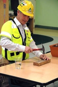 Kulka recreates pile driving on a small scale. He used the glass of water to illustrate how pounding creates vibration.
