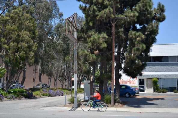 Bicyclist passes under a train signal structure on 20th Street in Santa Monica