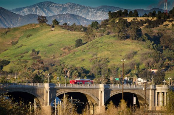 ART OF TRANSIT: A Metro Rapid bus crosses the Broadway bridge over the Los Angeles River on Wednesday afternoon, the day after a storm greened the local hills and dumped snow in the San Gabriel Mountains. Click above to see larger. Photo by Steve Hymon/Metro.