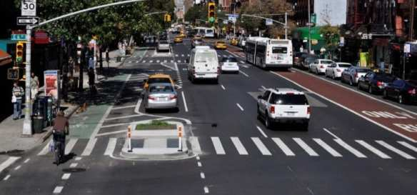1st Street in New York after a makeover. A bus lane at right was added and at left, the parking lane was moved away from the sidewalk as a way to protect a new bike lane from the general traffic lanes. Photo: New York City DOT.
