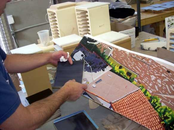 Artisan at artwork fabricator's shop comparing ceramic tile color to original artwork scan for execution in hand-glazed, hand-cut ceramic mosaic.  Photo: Mosaika Art & Design