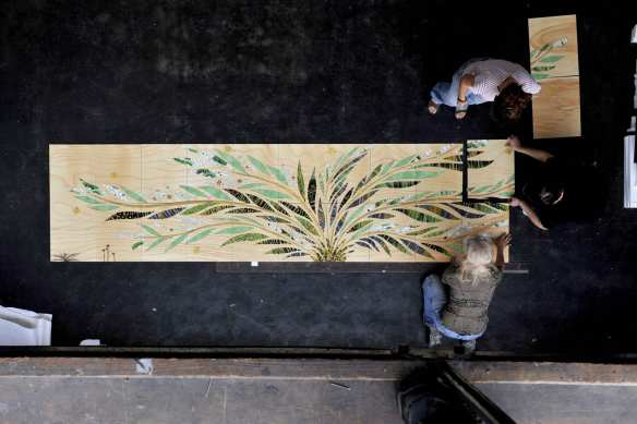 Artisans hand laying mosaic pieces into ceramic tile.  Photo Credit: Mayer of Munich