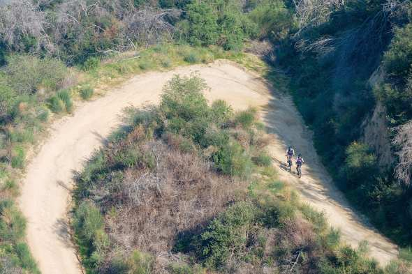 ART OF TRANSIT, ALMOST THE WEEKEND EDITION: A pair of cyclists climb the fire road between the Angeles National Forest ranger station on Highway 2 and Mt. Lukens. Photo by Steve Hymon.