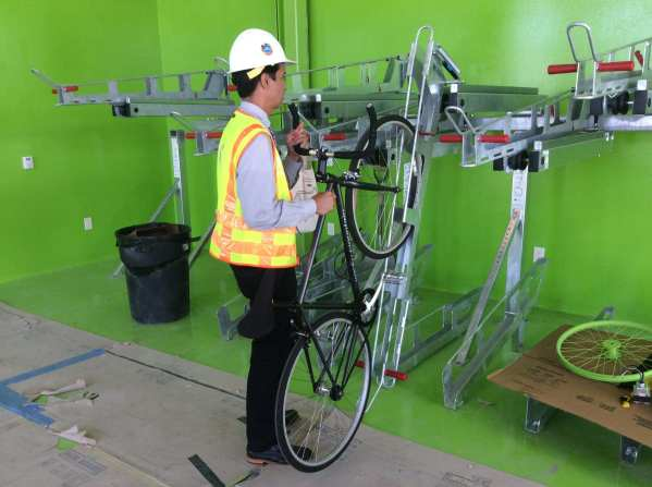 Anthony Jusay with Metro's Bike Program demonstrates how to load a bike onto the racks.