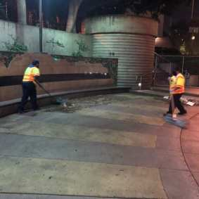 Metro staff clearing area near subway portal in preparation for reopening.