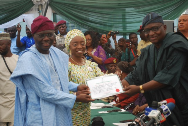 Mr. Babajide Sanwo-Olu receiving certificate of returns from Dr. Adekunle Ogunmola