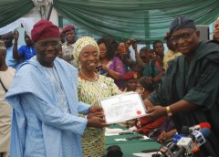 Mr. Babajide Sanwo-Olu receiving certificate of returns from Dr. Adekunle Ogunmola