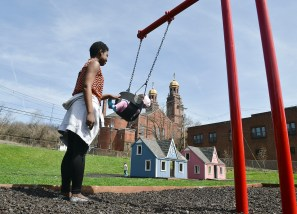 Shawntay Thompson pushes her daughter, Dayla, in a swing at a Braddock park.