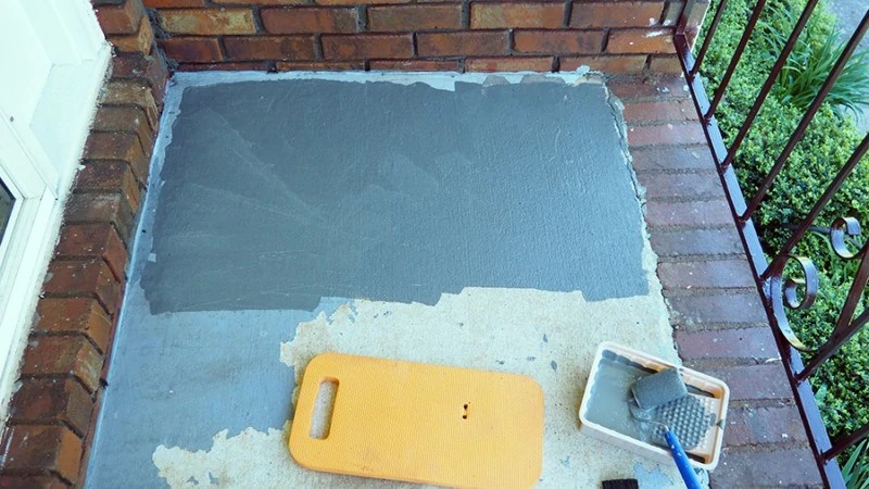 I used a pint brush to paint next to eh brick and a small roller to paint the main portion of the cement on the porch. A small knee board saved my knees! | via The Spirited Violet