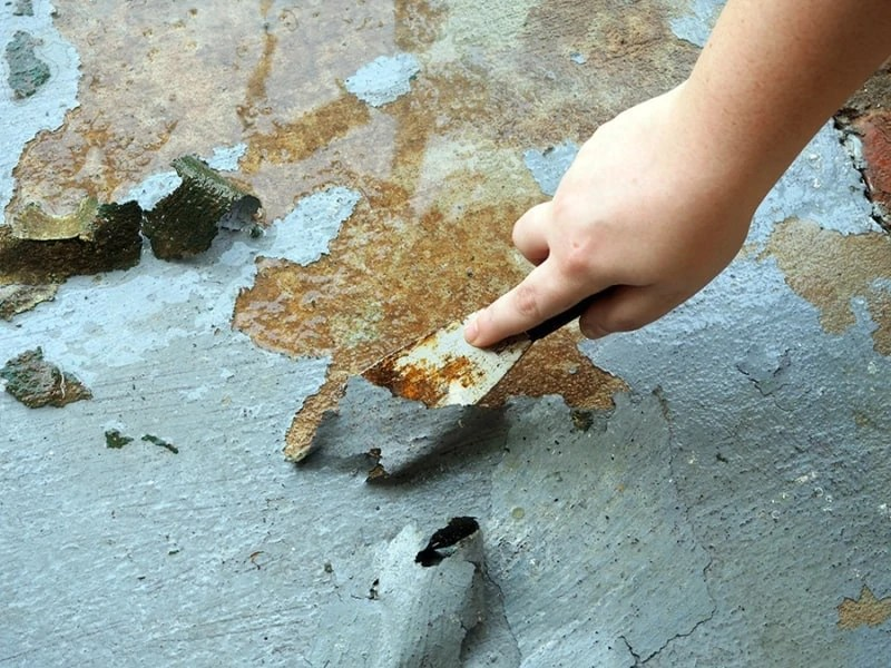 I am using a metal putty knife to strip paint off of our concrete with a water hose sprayer. I can already tell it is going to look a lot better! | via The Spirited Violet
