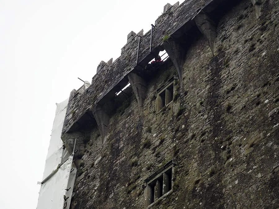 That is the infamous Blarney stone where you can see someone leaning back to kiss the stone. The stone is 90 feet above ground.   via The Spirited Violet