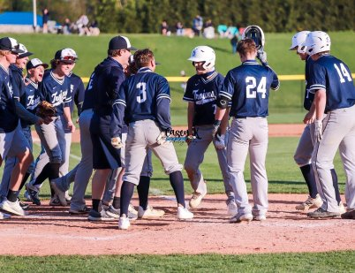 Gavin Kissel (7, center) is congratulated by his Chambersburg teammates after belting a grand slam during the Trojans' 13-7 win over Greencastle-Antrim on Monday (photo by Casey Kauffman).