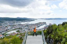 View from Mount Fløyen, overlooking Bergen, Norway. A victorious pose after skipping the floibanen to hike up the hill.