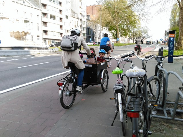 This is a picture of a lady riding a cargo bike with kids in the front