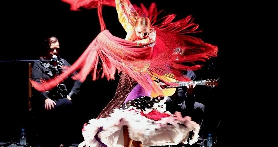 A woman dancing flamenco in a bright red dress