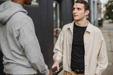 multiracial male teens talking on city street