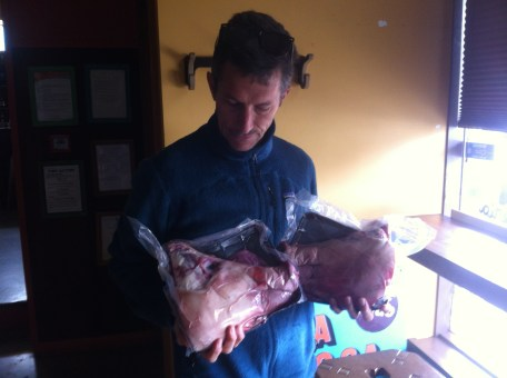 Lucas holding the pigs heads and looking squeamish.