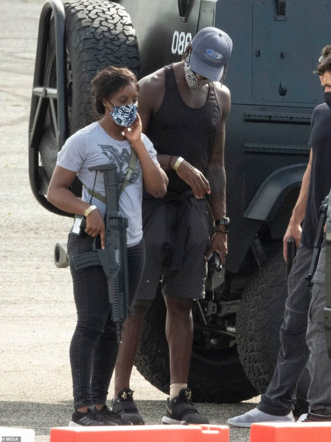 Action-packed: Other actors were seen on the set today carrying machine guns as they hopped out of black armoured vehicles