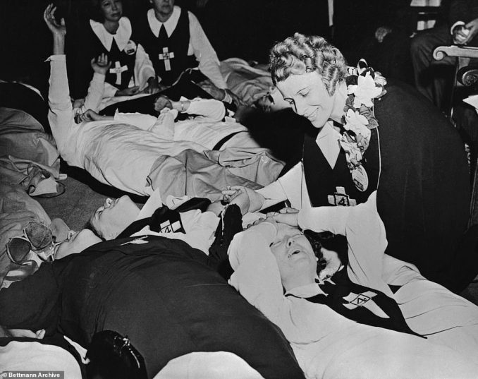 Sister Aimee Semple McPherson is shown ministering to parishioners as they became overcome with a religious fervor during a Four Square Gosepel sermon at the Angelus Temple Los Angeles. McPhersosn urged the delegates to 'worship with the heartfelt abandon of old time revivals.' They did