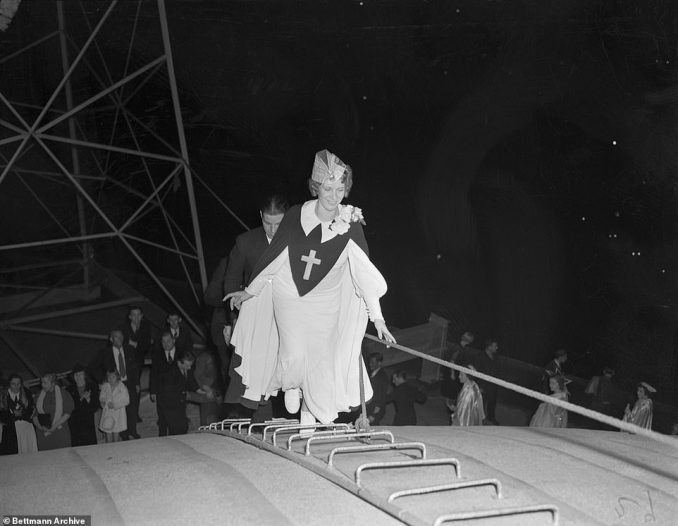 Aimee Semple McPherson and son Rolf, mount a ladder to the roof of Angelus Temple in Los Angeles, where she burned papers representing liquidated debts of $66,505 against the church as a publicity stunt
