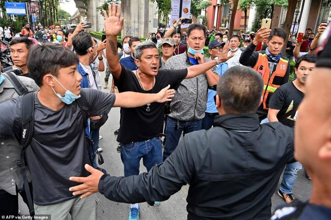 Activists hold their hands up to police showing their peaceful intentions as protests continue in Bangkok for a second day