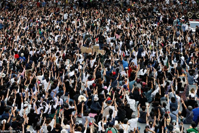 People show the three-finger salute during anti-government protests in Bangkok