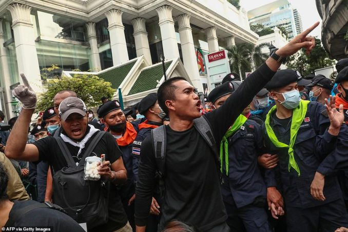 A pro-democracy protester gestures in front of the police in Bangkok as clashes broke out