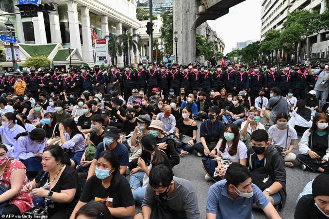 Police officers surround a group of seated demonstrators as they occupy part of central Bangkok to protest the government
