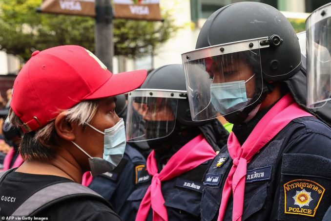 Police and protesters come face-to-face at an intersection in downtown Bangkok that has become a focal point of the second day of anti-government demonstrations