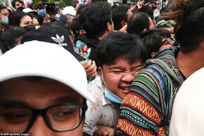A demonstrator has his face squashed as police try to push back the crowd in downtown Bangkok