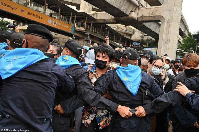 Police stand arms linked as they face off with pro-democracy protesters in Bangkok