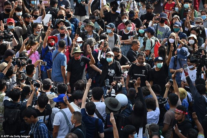 Pro-democracy protesters hold up the three-finger salute gather on a traffic intersection in Bangkok