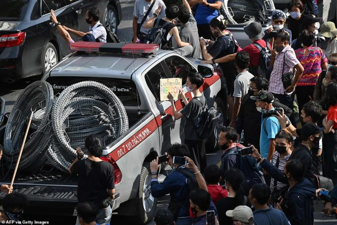 A pro-democracy protester holds up a sign next to a police vehicle carrying barbed wire during a rally