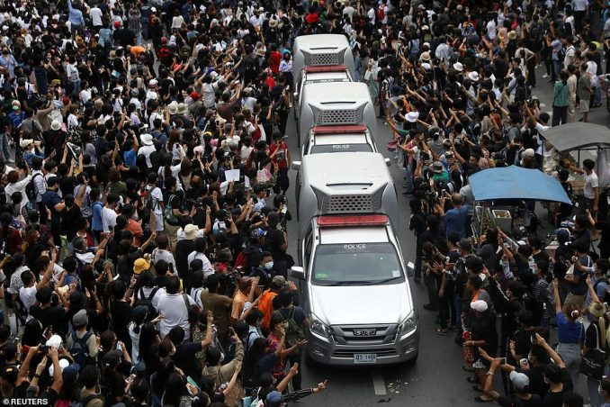 Police cars are seen among people showing the three-finger salute during anti-government protests