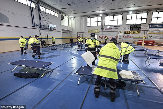 The staff of civil protection prepare the beds for the field hospital for possible COVID-19 patients in Turin, Italy, on Thursday