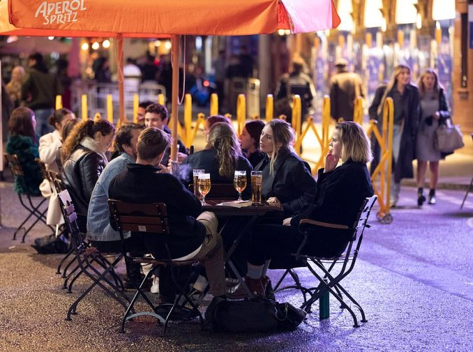 Friends gather around tables in Soho, London, and enjoy the final night out in the capital before tighter restrictions are imposed