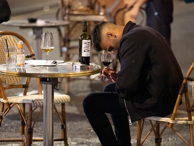 One pub-goer clutches a glass of red wine and looks at his lap outside a bar in Soho, London, before coronavirus restrictions are tightened