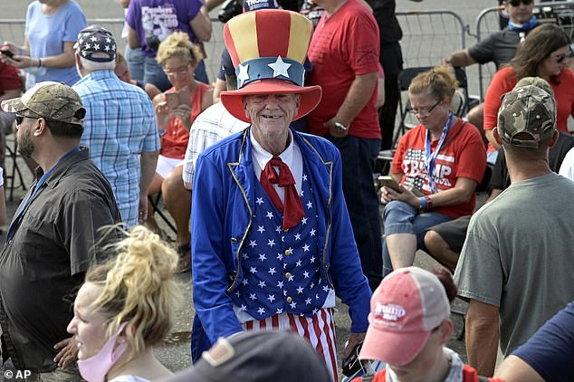 A supporter of President Donald Trump walks through the crowd at the airport while dressed as Uncle Sam