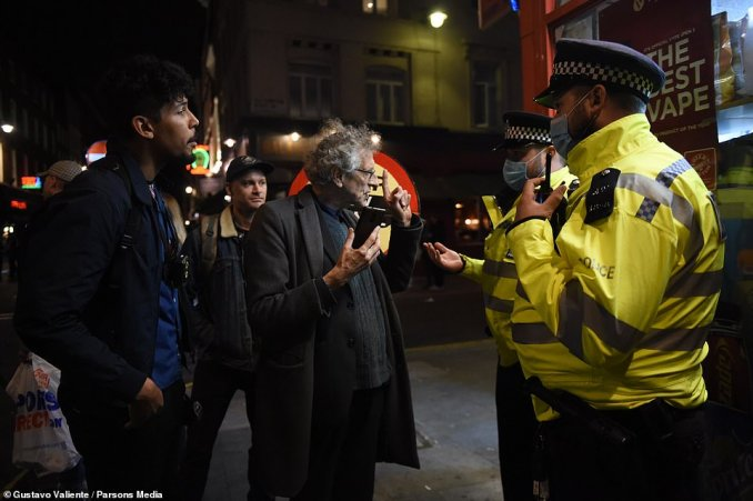 Piers Corbyn held up a finger as he spoke to police officers in Soho. The conversation appeared to be animated as the police officer held out a hand
